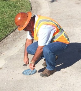 pulling valve box cover to inspect valve box for debris before he cleans it via air / vacuum excavation.